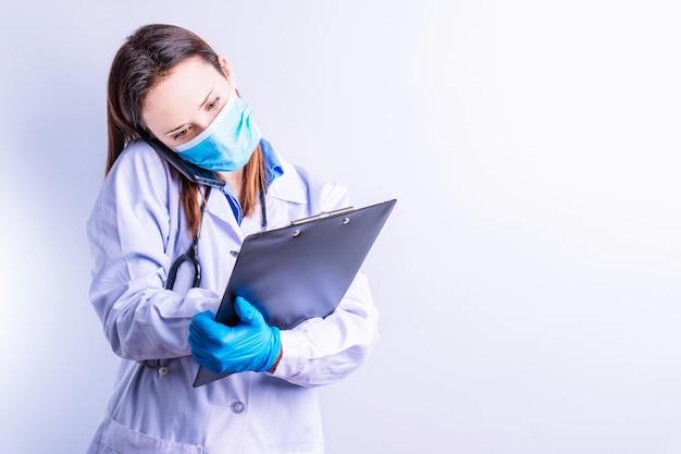 Jonge mooie doktersvrouw die tweedelige toga's draagt met een masker die aan de telefoon praat met een patiënt die een rapportconcept schrijft, bezoek medische telefoon online geneeskunde en technologieconcept