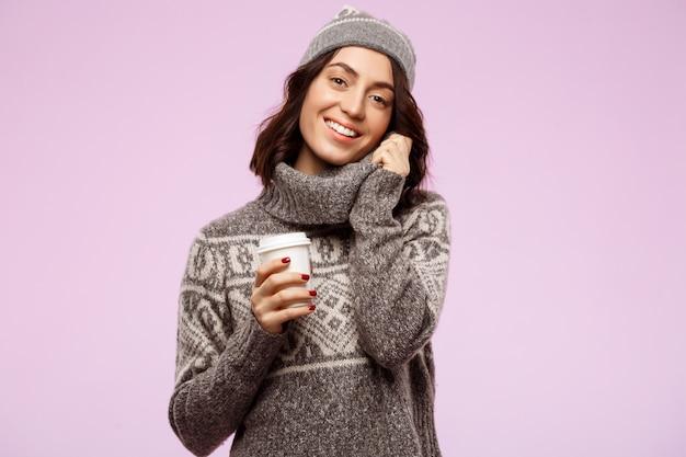 Jonge mooie donkerbruine meisje het glimlachen holdingskoffie over lichte muur