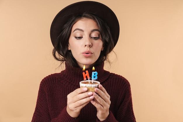 Jonge mooie donkerbruine vrouw die over beige muurmuur wordt geïsoleerd die cupcake houdt die gelukkige verjaardagskaarsen uitblazen.