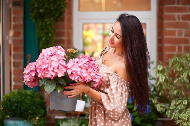 Jonge mooie donkerbruine vrouw die roze bloemen houdt