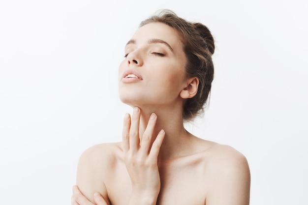 Jonge mooie donkerharige blanke vrouw met knot kapsel en naakte schouders overvallen hoofd met gesloten ogen aanraken nek. meisje dat lichaamscrème na bad gebruikt.