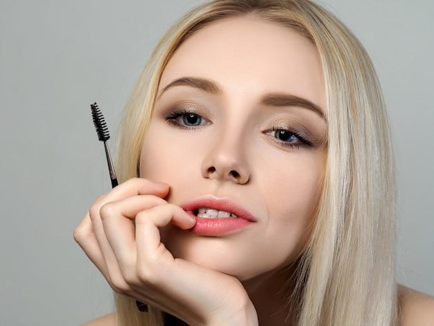 Jonge mooie doordachte blonde vrouw die de spiegel bekijkt en een wenkbrauwborstel houdt