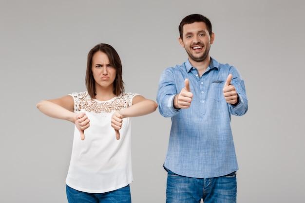 Jonge mooie echtpaar poseren over grijze muur