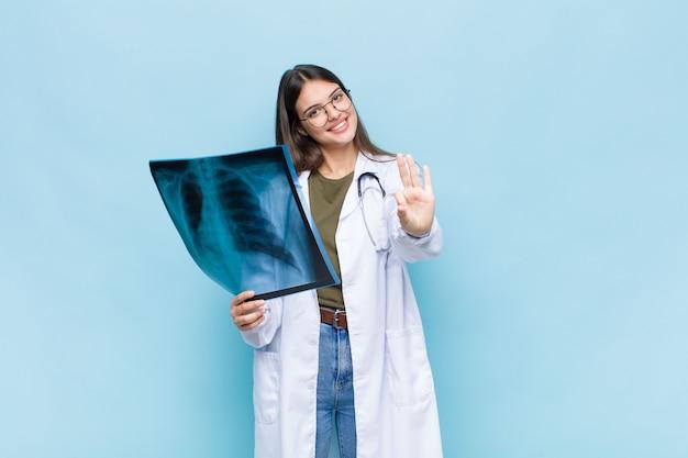 Jonge mooie en arts die vriendelijk glimlacht kijkt, nummer drie of derde met vooruit hand toont, aftellend