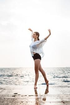 Jonge mooie en ballerina die buiten dansen stellen
