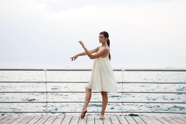 Jonge mooie en ballerina die, zeedijk buiten dansen stellen