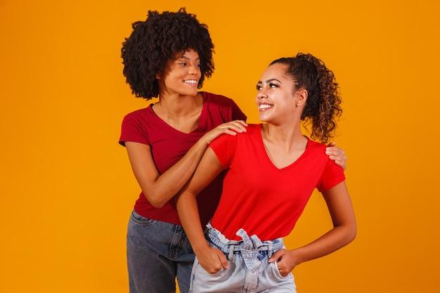 Jonge mooie en gelukkige afro vrouwelijke vrienden die naar de camera glimlachen. Premium Foto