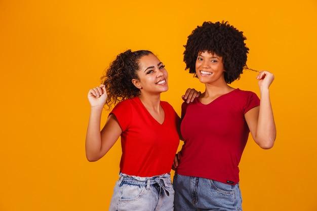 Jonge mooie en gelukkige afro vrouwelijke vrienden die naar de camera glimlachen.