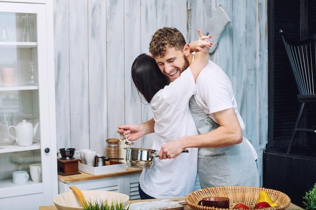 Jonge mooie en gelukkige paar man en vrouw thuis in de keuken in de ochtend doen ontbijt