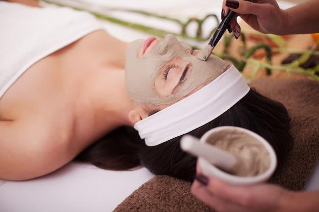 Jonge, mooie en gezonde vrouw in spa salon. traditionele oosterse massagetherapie en schoonheidsbehandelingen.