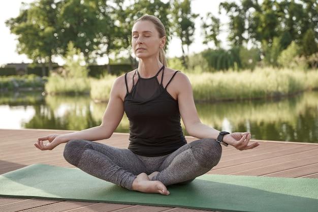 Jonge, mooie en gezonde vrouw in sportkleding zittend in lotushouding op een mat en mediteren terwijl