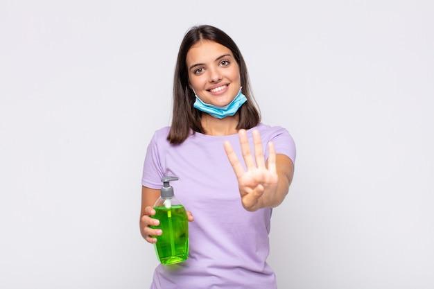 Jonge mooie en vrouw die vriendelijk glimlacht kijkt, nummer vier of vierde met vooruit hand toont, aftellend