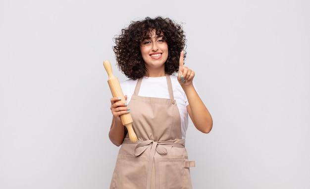 Jonge mooie en vrouwenchef-kok die vriendelijk glimlacht kijkt, nummer één toont of eerst met vooruit hand, aftellend