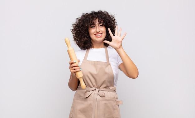 Jonge mooie en vrouwenchef-kok die vriendelijk glimlacht kijkt, nummer vijf of vijfde met vooruit hand toont, aftellend