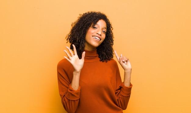 Jonge mooie en zwarte die vriendelijk glimlachen kijken, nummer zes of zesde met vooruit hand tonen, die over oranje muur aftellen