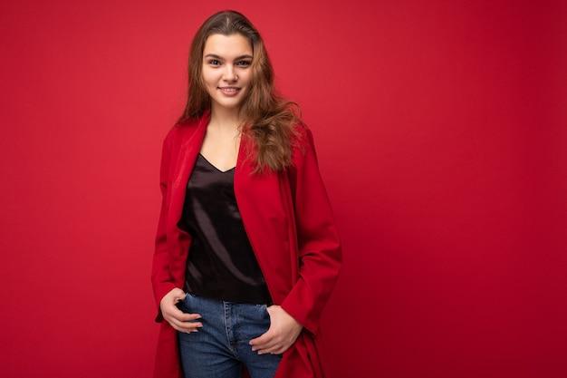 Jonge mooie europese stijlvolle brunette vrouw, gekleed in zwarte blouse top en rode cardigan geïsoleerd