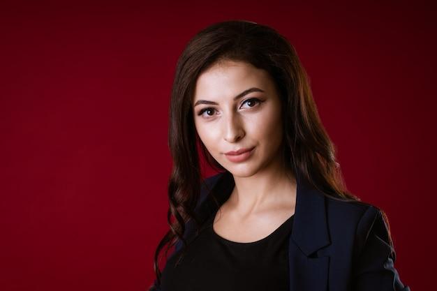 Jonge mooie europese stijlvolle brunette vrouw in zwarte blouse en donkerblauw jasje geïsoleerd op rood...
