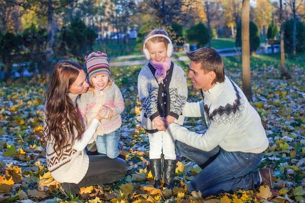 Jonge mooie familie van vier genoten van het ontspannen in de herfstpark
