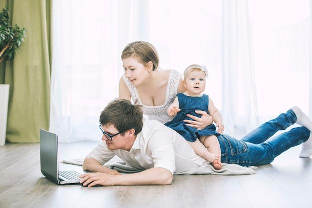 Jonge mooie familiemoeder, vader en dochter thuis samen met laptop