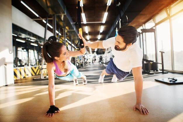 Jonge mooie fitness paar glimlachend en handen klappen elkaar tijdens het doen van push-ups samen in de sportschool.
