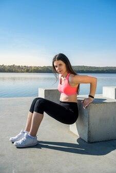 Jonge mooie fitness vrouw doet yoga houdingen, streching in de natuur