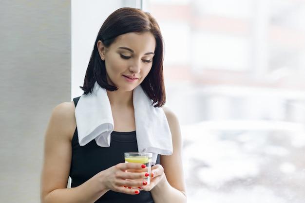 Jonge mooie fitness vrouw in sportkleding met handdoek