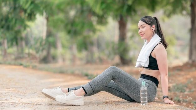 Jonge mooie fitness vrouw in sportkleding zittend op de grond na het sporten buiten.