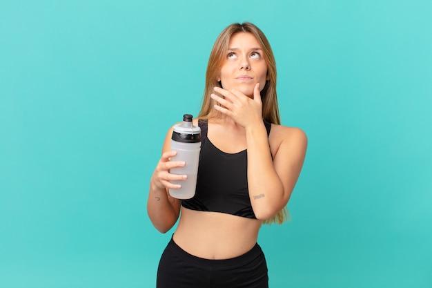 Jonge mooie fitnessvrouw denkt, voelt zich twijfelachtig en verward