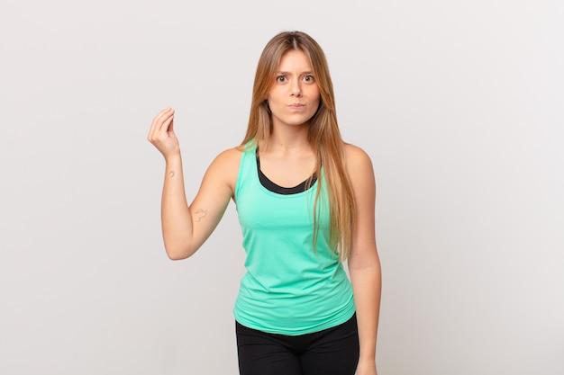 Jonge mooie fitnessvrouw die capice of geldgebaar maakt en zegt dat je moet betalen