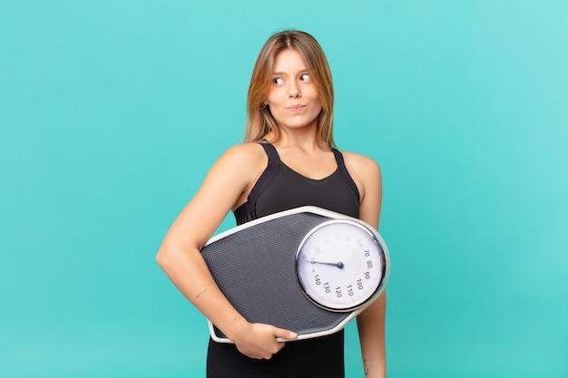 Jonge mooie fitnessvrouw die haar schouders ophaalt, zich verward en onzeker voelt