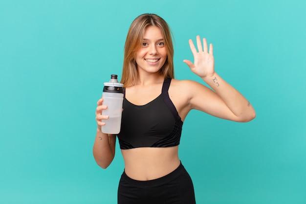 Jonge mooie fitnessvrouw die lacht en er vriendelijk uitziet, met nummer vijf
