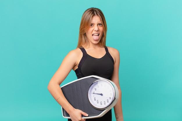 Jonge mooie fitnessvrouw die walgt en geïrriteerd voelt en tong uitsteekt?