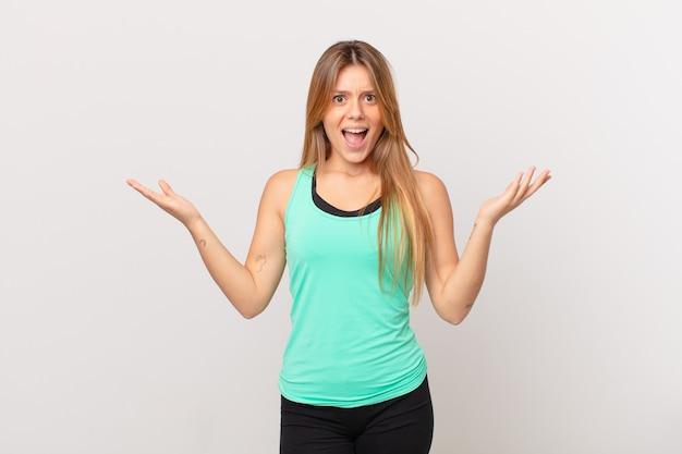 Jonge mooie fitnessvrouw die zich gelukkig en verbaasd voelt over iets ongelooflijks