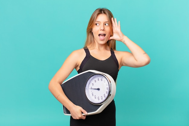 Jonge mooie fitnessvrouw die zich gelukkig, opgewonden en verrast voelt