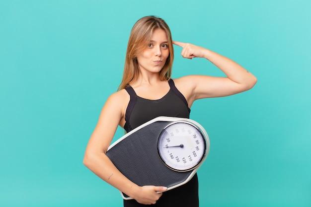 Jonge mooie fitnessvrouw die zich verward en verbaasd voelt en laat zien dat je gek bent