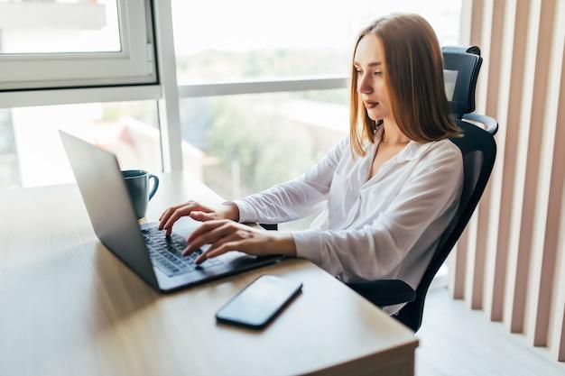 Jonge mooie freelance vrouw die aan laptop op kantoor aan huis werkt