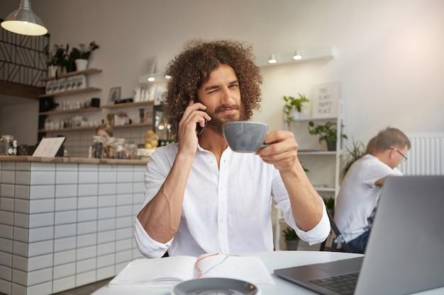 Jonge mooie gekrulde man met weelderige baard vrolijk glimlachend en knipoog geven, koffie drinken tijdens telefoongesprek, werken in openbare ruimte met laptop