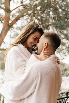 Jonge mooie gelukkig pasgetrouwden verliefd op een man en een vrouw in witte badjassen op het balkon van het huis glimlach en knuffel