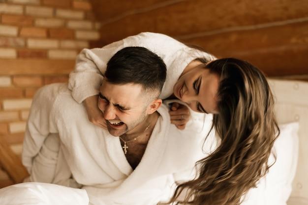 Jonge mooie gelukkig pasgetrouwden verliefd op een man en een vrouw liggen in bed, glimlachen en knuffelen in het huis