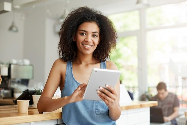 Jonge mooie gelukkige afrikaanse vrouw die in koffie het glimlachen holdingstablet rusten.