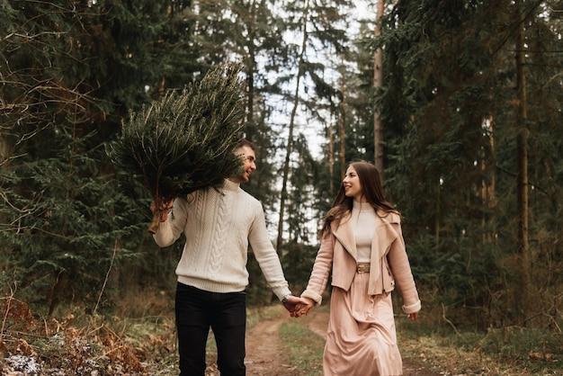 Jonge mooie gelukkige geliefden man en vrouw, liefdesverhaal in de winter met een levende kerstboom in een dennenbos in de zon