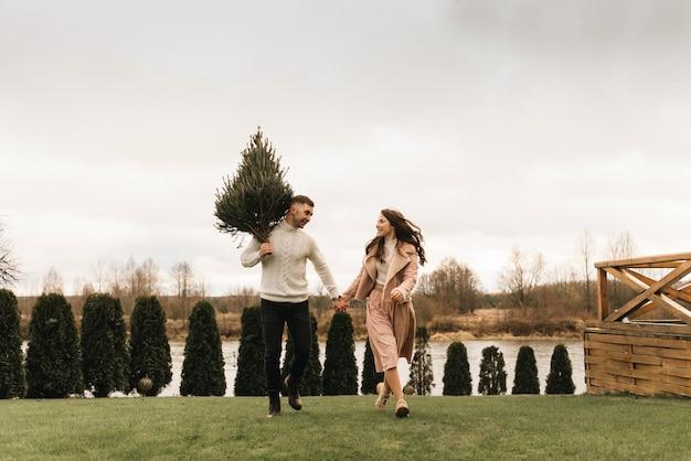 Jonge mooie gelukkige geliefden man en vrouw, liefdesverhaal in de winter met een levende kerstboom in hun handen op de achtergrond van de rivieroever