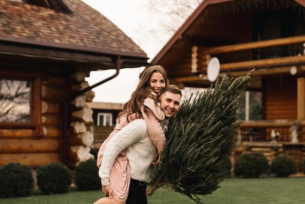 Jonge mooie gelukkige geliefden man en vrouw, liefdesverhaal in de winter met een levende kerstboom in hun handen op de achtergrond van een houten huis