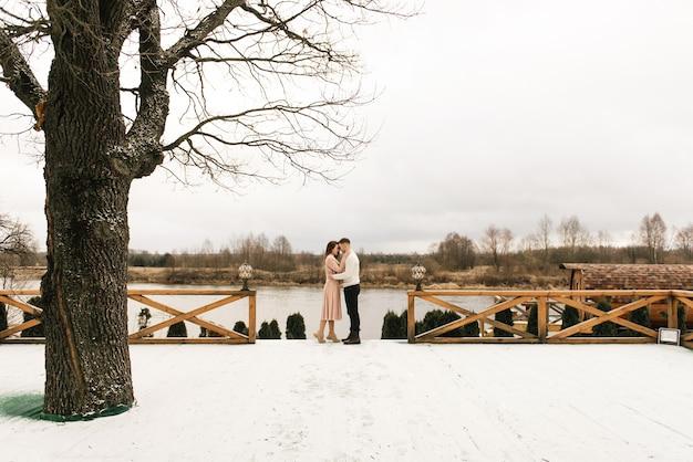 Jonge mooie gelukkige geliefden man en vrouw, liefdesverhaal in de winter met sneeuw op een pittoreske plek