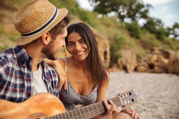 Jonge mooie gelukkige paar gitaar spelen zittend op het strand