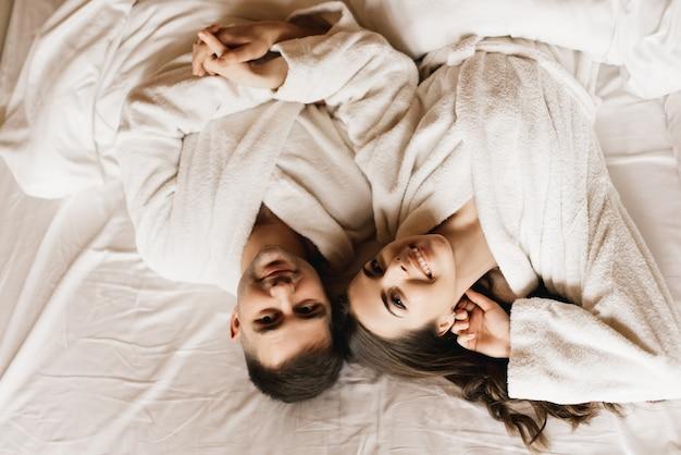 Jonge mooie gelukkige pasgetrouwden verliefd een leugen in bed
