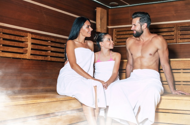 Jonge mooie gelukkige vader en moeder met kleine schattige dochter in de badhanddoeken zijn ontspannen in de hete sauna