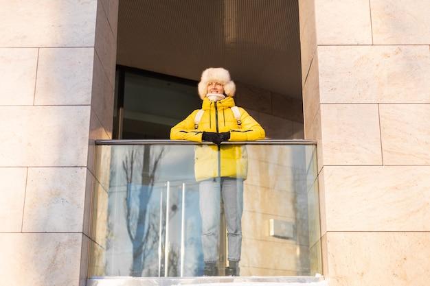 Jonge mooie gelukkige vrouw buitenshuis op een zonnige dag in warme kleren en een rugzak van de winter russische siberische hoed door de stad reizen