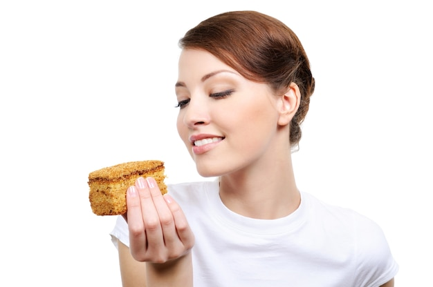 Jonge mooie gelukkige vrouw die geïsoleerde cake eet