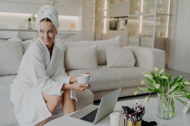 Jonge mooie gelukkige vrouw in badjas met kopje thee of koffie voelt zich ontspannen na het nemen van een douche of bad thuis, zittend op de bank in de woonkamer en opzij kijkend terwijl u op laptop werkt